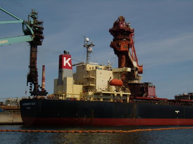 大型船に覆いかぶさるような迫力の鉱石揚げ荷装置たち