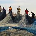 網をたたむ漁師たち