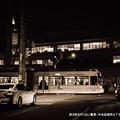 写真: 夜の町を行く白い電車。